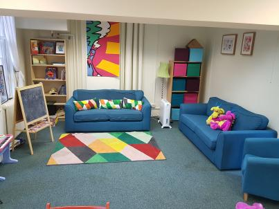 Image description: Child contact centre, two sofas, toys, bright coloured rug and wall hangings